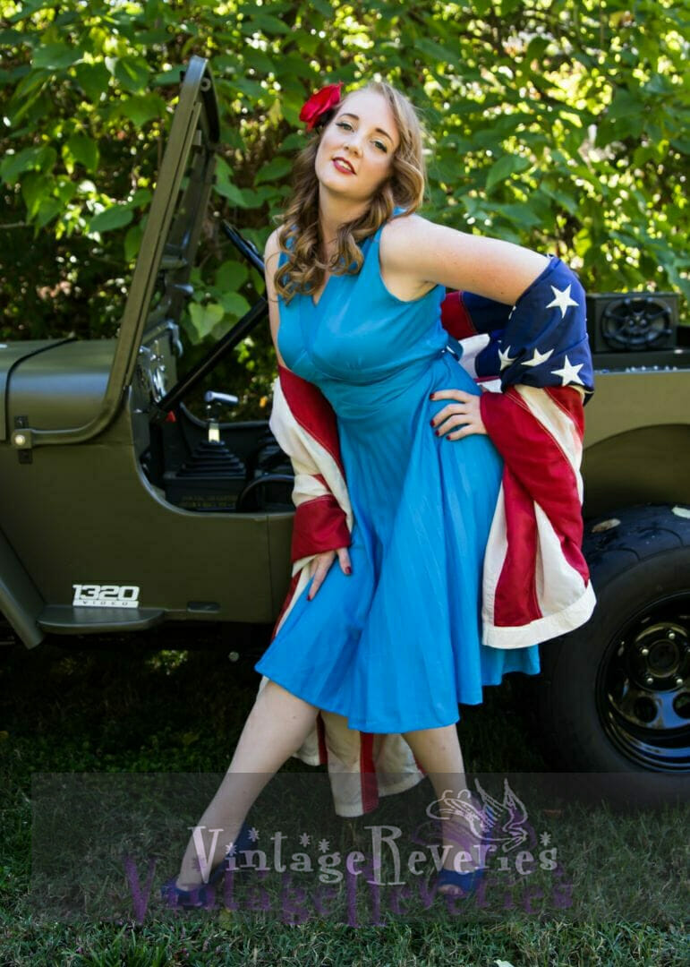 pinup model draped in a flag with a jeep
