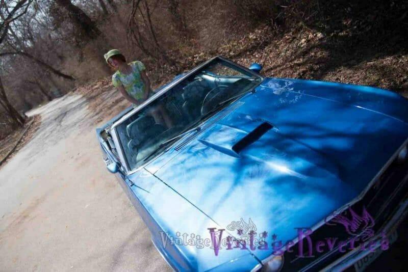 sitting in a big blue vintage car